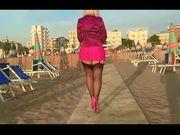 Zoccola camminando per la spiaggia in autoreggenti