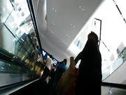 Upskirt sulla scala mobile del supermercato